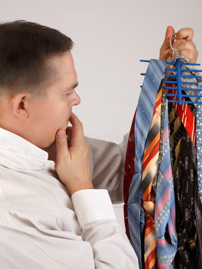 Hombre joven indeciso que mira a muchas corbatas fotos de archivo libres de regalías