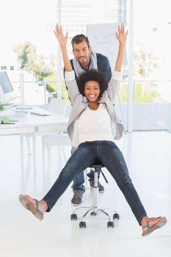 Hombre joven juguetón que empuja a la mujer en silla en oficina fotografía de archivo libre de regalías