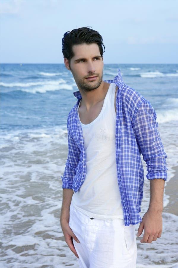 Hombre joven latino mediterráneo en la playa fotos de archivo
