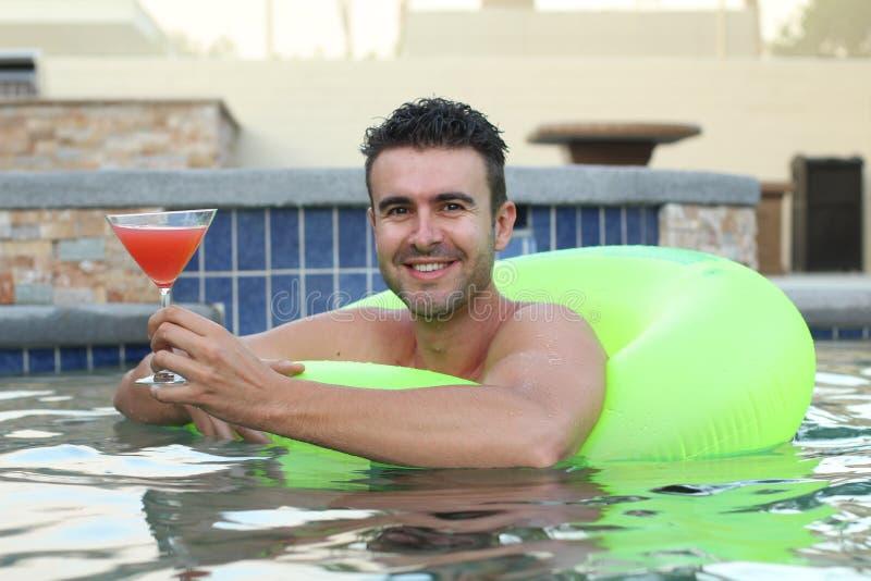 Hombre joven lindo que bebe un cóctel mientras que se relaja en una piscina foto de archivo libre de regalías