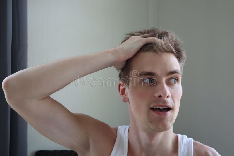 Hombre joven llevar a cabo su cabeza con una mano Retrato del hombre joven atractivo con la expresión satisfecha Fondo blanco por imágenes de archivo libres de regalías