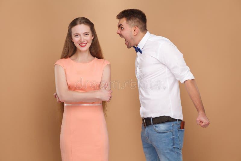 Hombre joven loco en la camisa blanca que coloca y que grita en la mujer i fotos de archivo libres de regalías