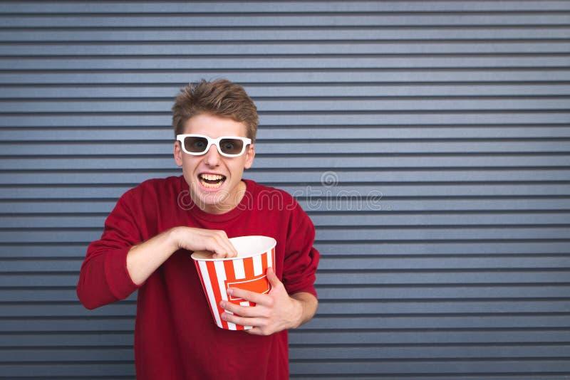 Hombre joven loco en los vidrios 3D que come la taza de las palomitas y que mira la cámara contra un fondo oscuro foto de archivo