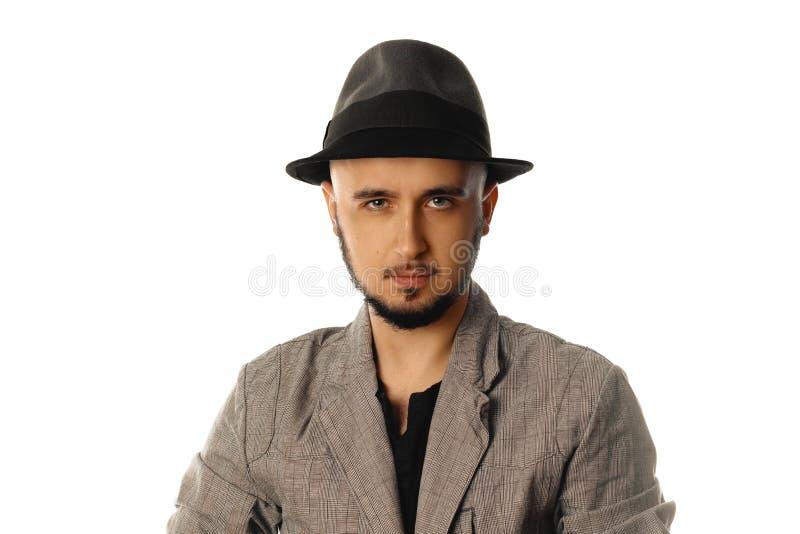 Hombre joven magnífico en el sombrero y la chaqueta que miran la cámara imágenes de archivo libres de regalías