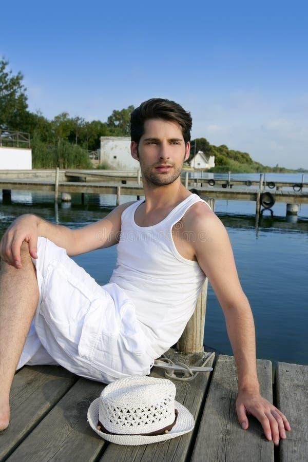 Hombre joven mediterráneo relajado en el embarcadero de madera foto de archivo