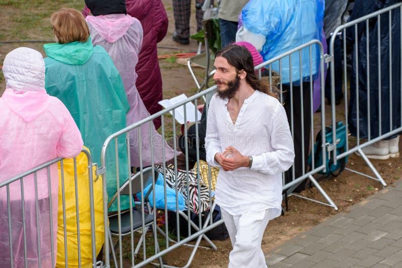 Hombre joven, mirada similar como Jesus Christ, durante masa santa en Aglona, Letonia imagen de archivo