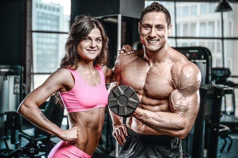 Hombre joven modelo y mujer que se resuelven en gimnasio imagen de archivo