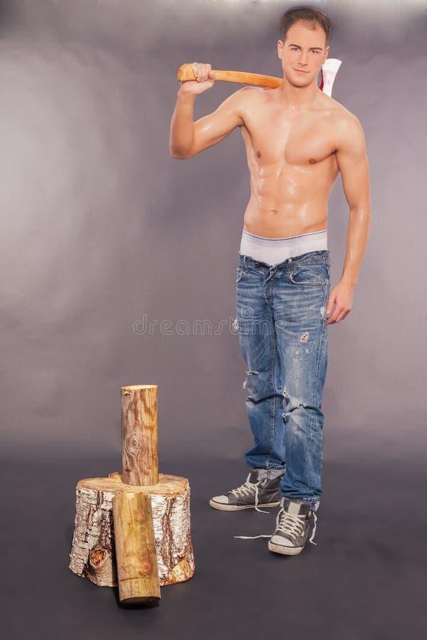 Hombre joven muscular atractivo que taja la madera del fuego fotografía de archivo libre de regalías