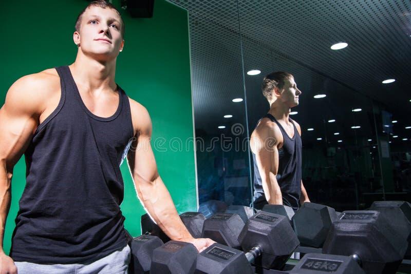 Hombre joven muscular cerca de la fila de la pesa de gimnasia imagen de archivo libre de regalías