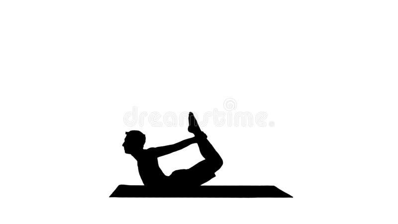 Hombre joven muscular deportivo de la yogui de la silueta que hace el ejercicio del backbend, dhanurasana, postura del arco imagen de archivo