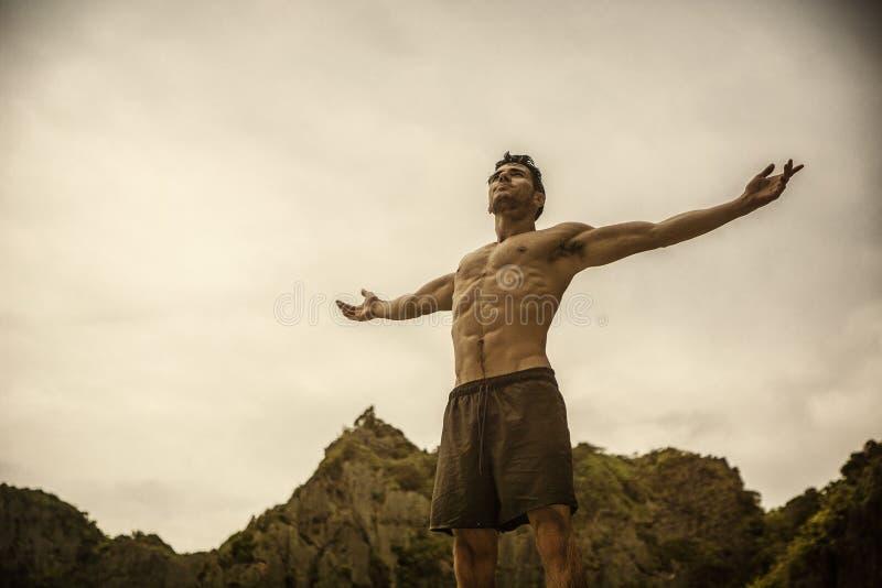 Hombre joven muscular en la playa que disfruta de la libertad fotografía de archivo