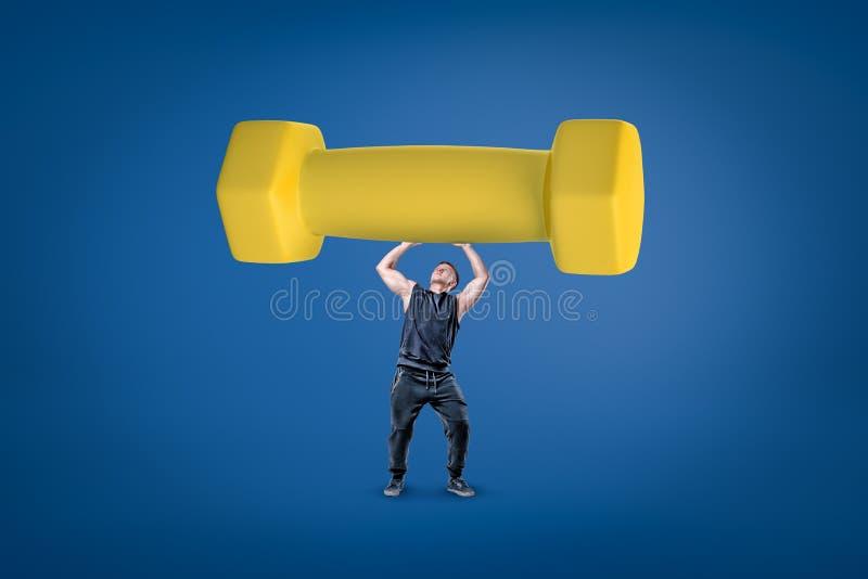 Hombre joven muscular fuerte que lleva a cabo una pesa de gimnasia amarilla grande en fondo azul fotos de archivo