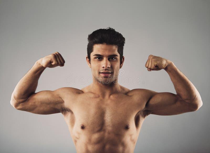 Hombre joven muscular que muestra apagado su cuerpo definido fotos de archivo