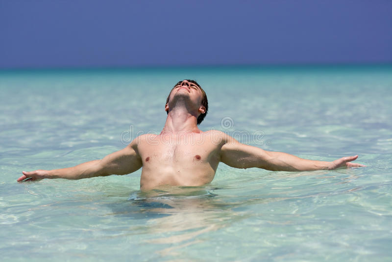 Hombre joven muscular que se relaja en el mar fotografía de archivo