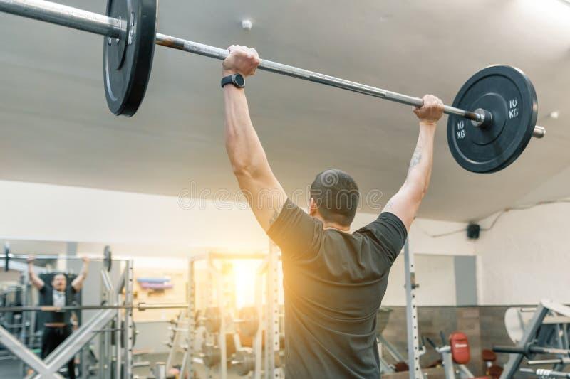 Hombre joven muscular que trabaja con los pesos pesados del barbell en gimnasio de entrenamiento Deporte, levantamiento de pesas, imagenes de archivo