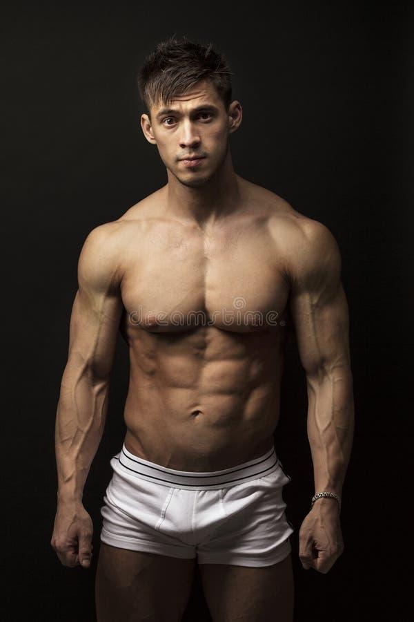 Hombre joven muscular sobre negro imágenes de archivo libres de regalías
