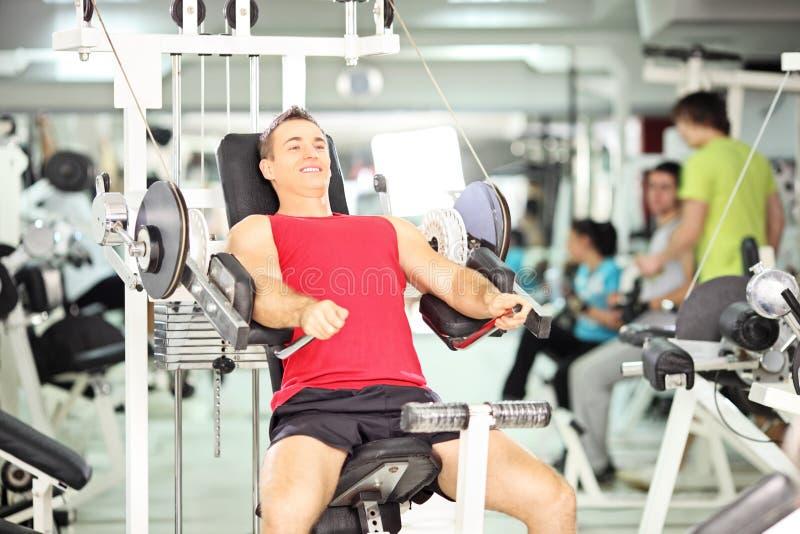 Hombre joven muscular sonriente que ejercita en un club fotos de archivo libres de regalías