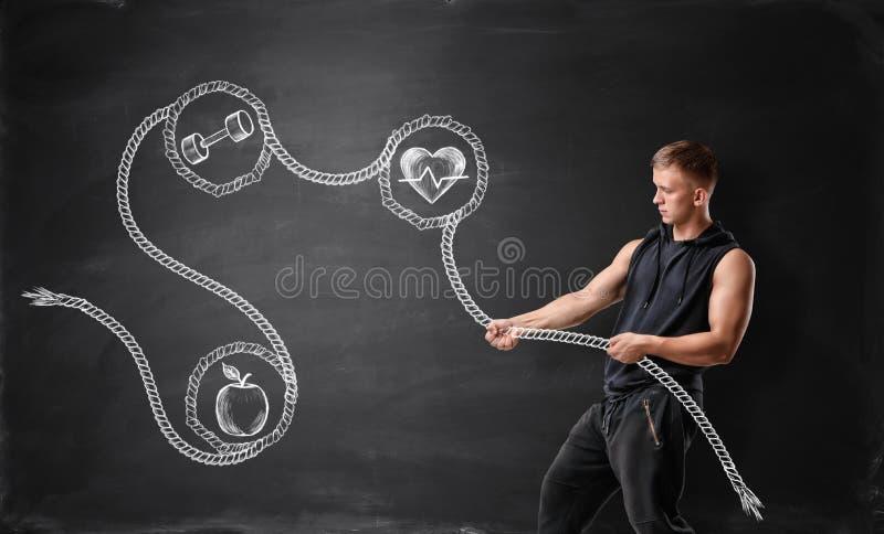 Hombre joven musculoso que tira de la cuerda dibujada con la manzana, pesa de gimnasia y batiendo el corazón fotografía de archivo libre de regalías
