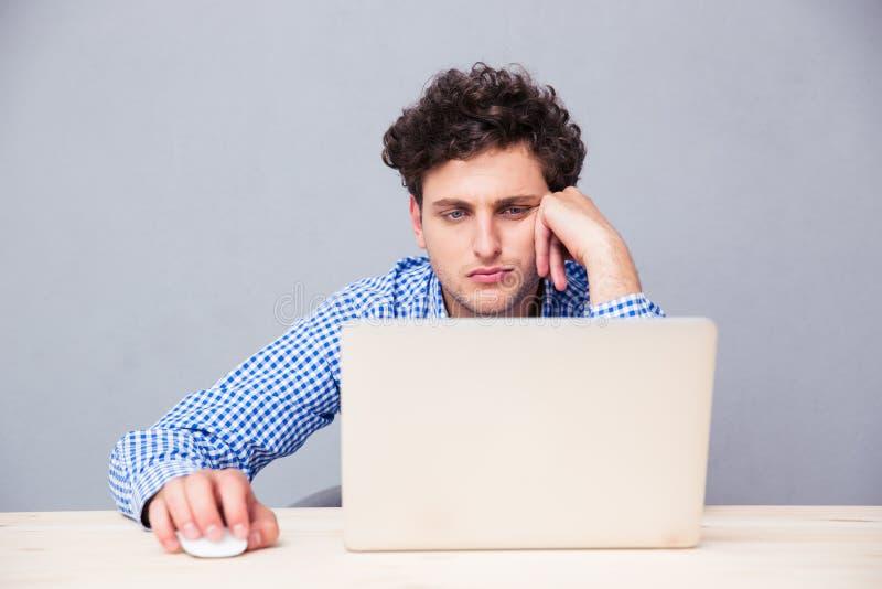 Hombre joven ocasional que usa la computadora portátil imagen de archivo