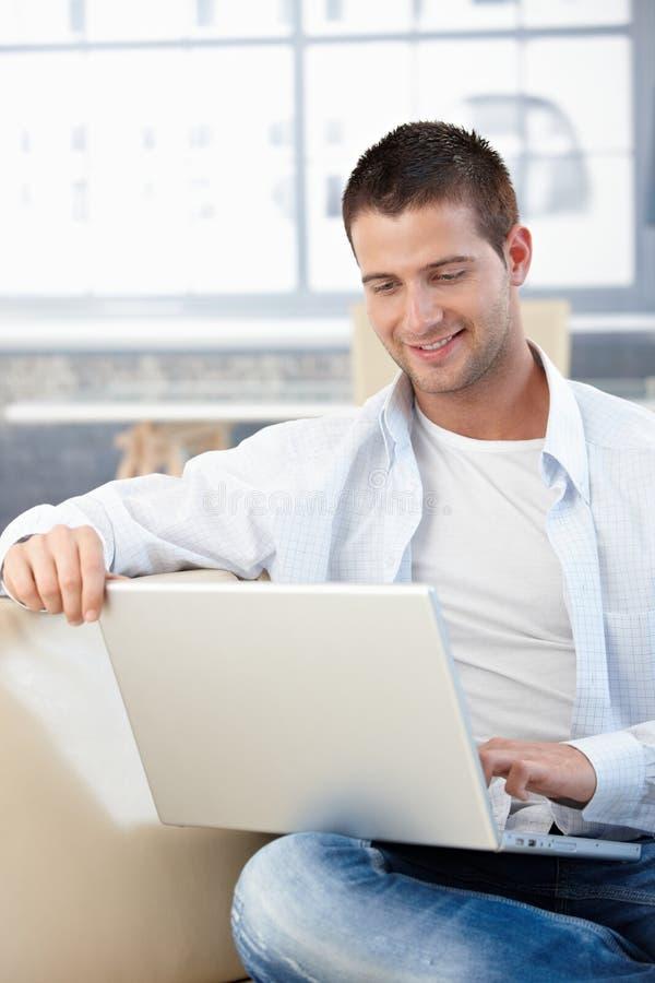 Hombre joven ocasional que usa la computadora portátil en el país que sonríe imágenes de archivo libres de regalías