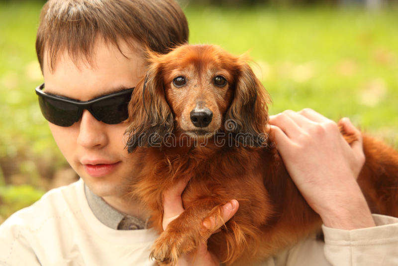 Hombre joven oculto con la perro-guía imagen de archivo libre de regalías