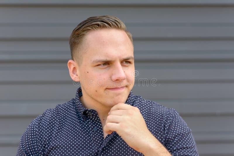 Hombre joven pensativo con su mano a su barbilla imagen de archivo libre de regalías