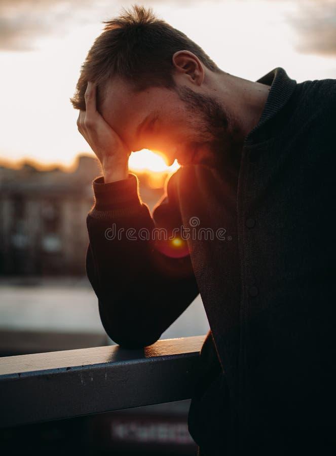Hombre joven pensativo en el fondo del paisaje urbano en la puesta del sol fotografía de archivo libre de regalías