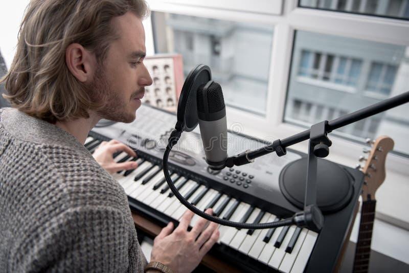 Hombre joven pensativo que realiza melodía en el sintetizador imágenes de archivo libres de regalías
