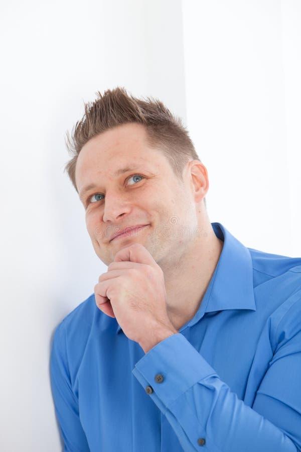 Hombre joven pensativo que se inclina en una pared foto de archivo