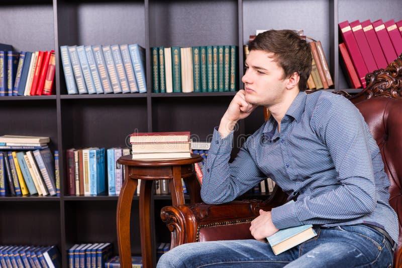 Hombre joven pensativo que se sienta en la silla en la biblioteca fotografía de archivo libre de regalías