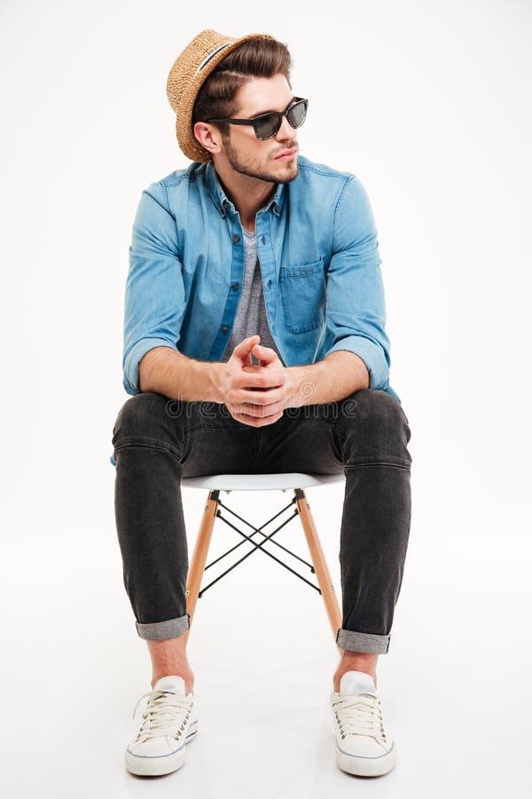 Hombre joven pensativo que se sienta en silla y el pensamiento imagen de archivo