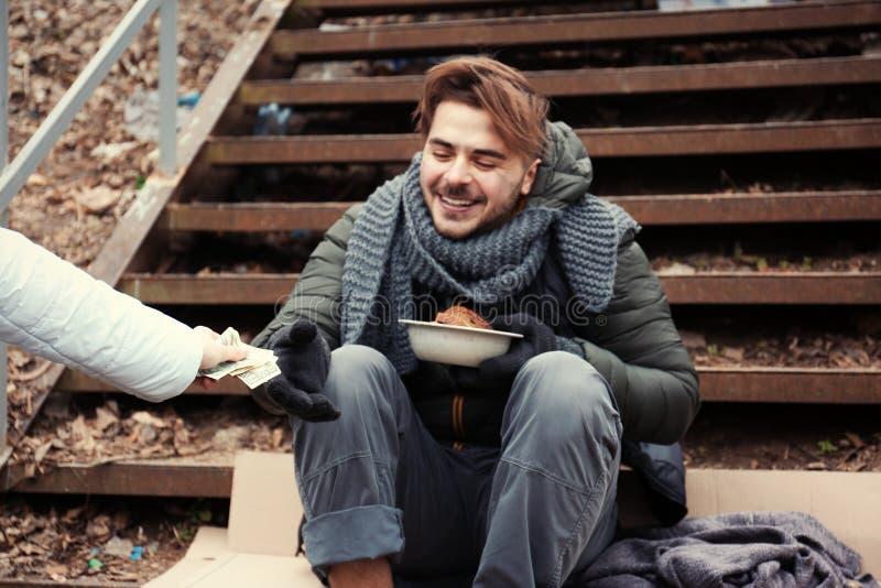 Hombre joven pobre que pide dinero en las escaleras al aire libre fotos de archivo libres de regalías