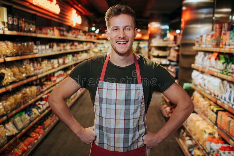 Hombre joven positivo alegre feliz en soporte del delantal en colmado entre shelfs Él presenta en cámara y sonrisa Solamente aden fotos de archivo libres de regalías