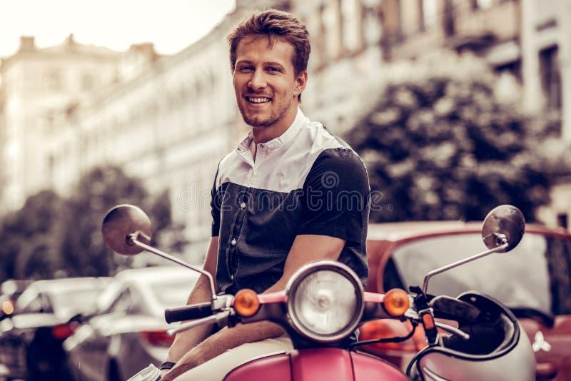 Hombre joven positivo alegre que sonr?e a usted imagen de archivo