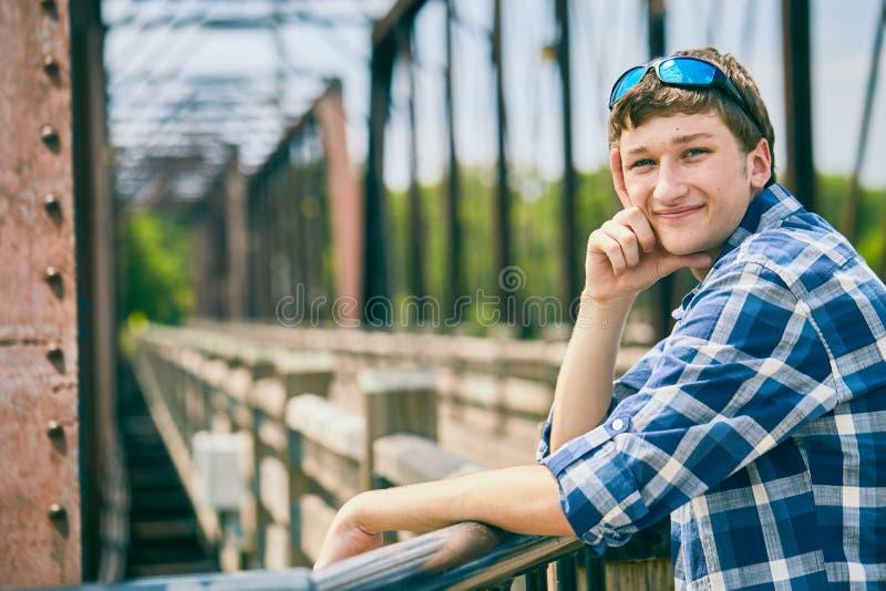 Hombre joven positivo que se coloca en el puente y la sonrisa fotos de archivo