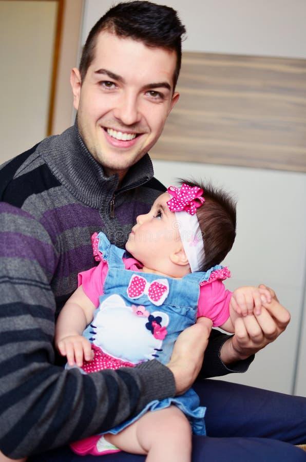 Hombre joven que abraza al bebé lindo foto de archivo libre de regalías