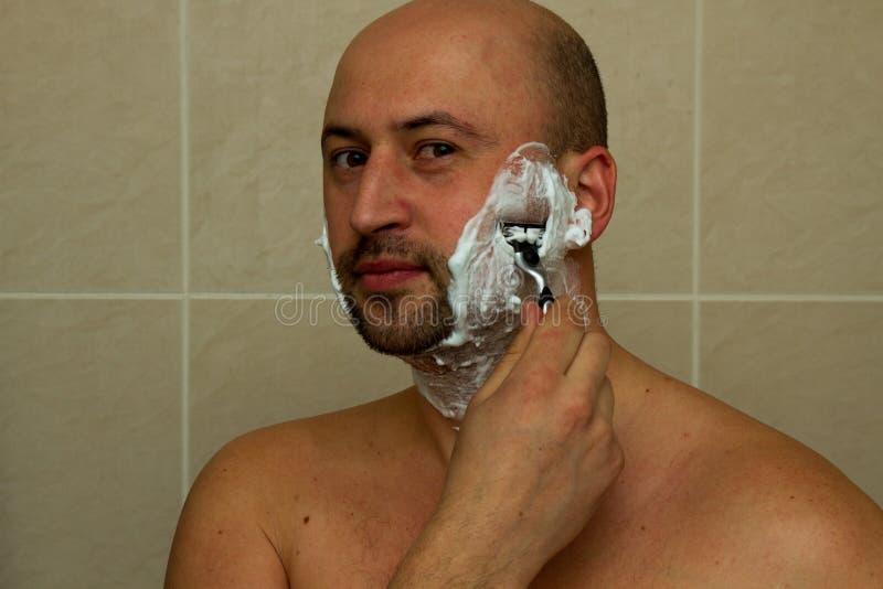 Hombre joven que afeita su barba con la maquinilla de afeitar reflejada fotografía de archivo libre de regalías