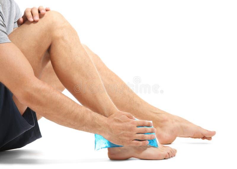 Hombre joven que aplica la compresa fría a la pierna imágenes de archivo libres de regalías