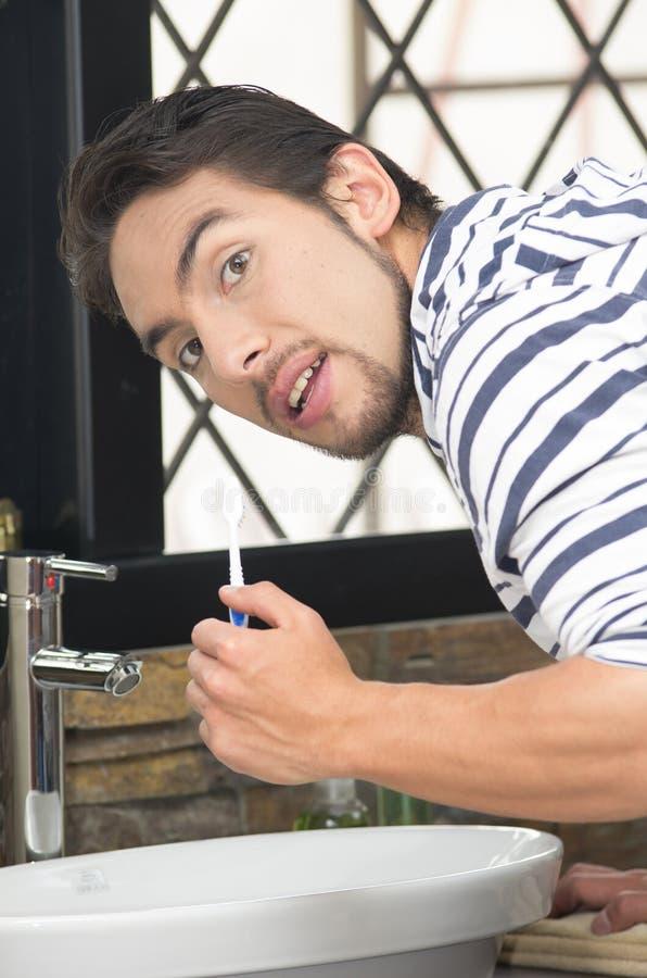 Hombre joven que aplica sus dientes con brocha imágenes de archivo libres de regalías