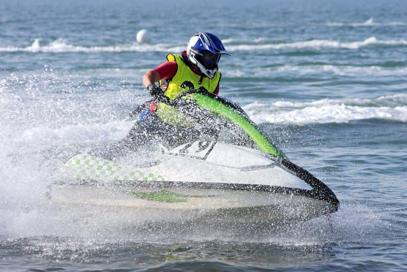 Hombre joven que apresura adelante en jetbike durante una raza foto de archivo