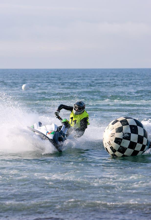 Hombre joven que apresura adelante en jetbike durante una raza imagen de archivo