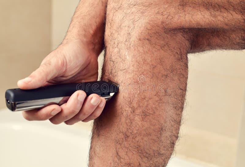 Hombre joven que arregla sus piernas con un condensador de ajuste eléctrico imagen de archivo libre de regalías