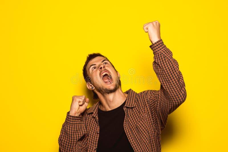 Hombre joven que aumenta sus brazos con la expresión de la victoria imagenes de archivo