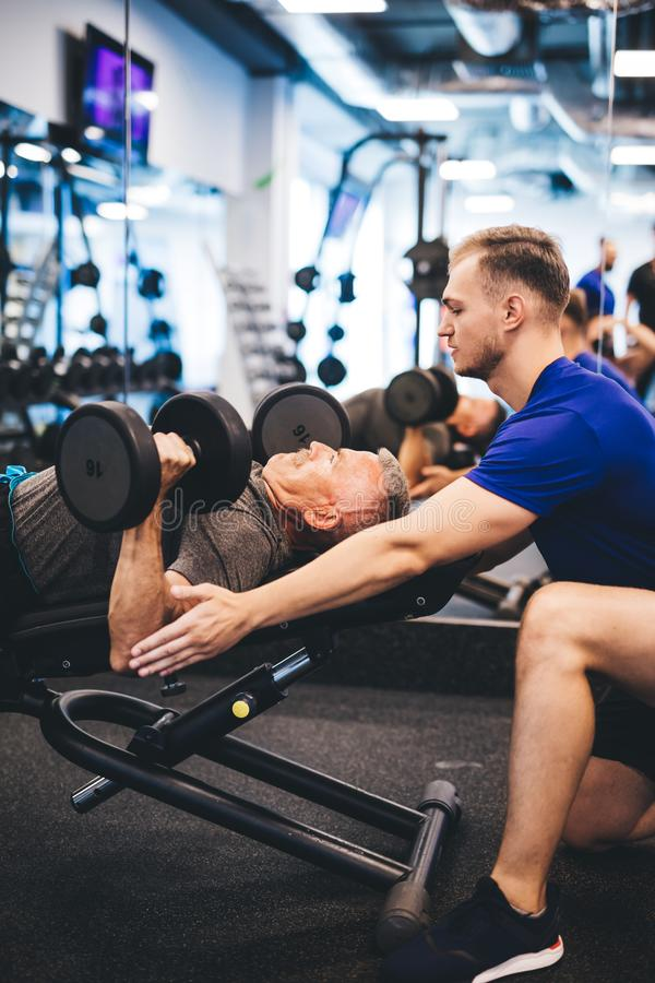 Hombre joven que ayuda al hombre mayor en el gimnasio fotografía de archivo