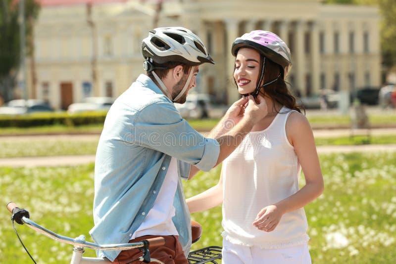 Hombre joven que ayuda a su novia a poner el casco de la bicicleta foto de archivo libre de regalías