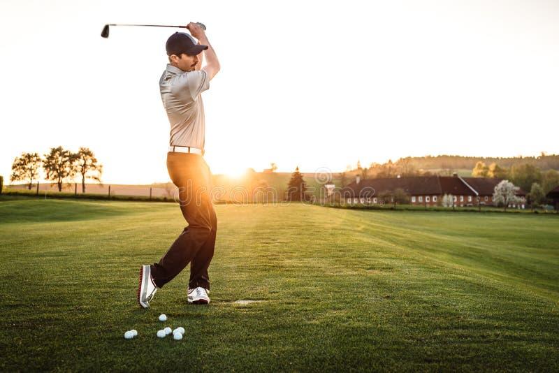 Hombre joven que balancea en el campo de golf fotos de archivo libres de regalías