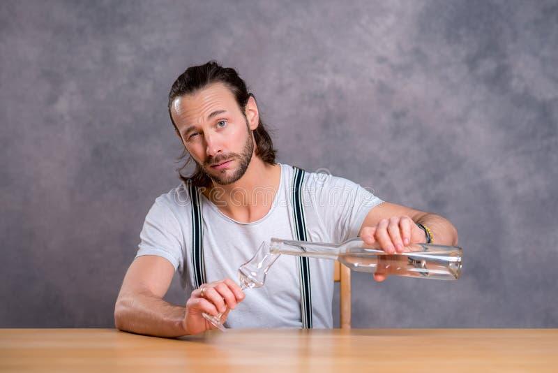 Hombre joven que bebe alcohol claro imagenes de archivo