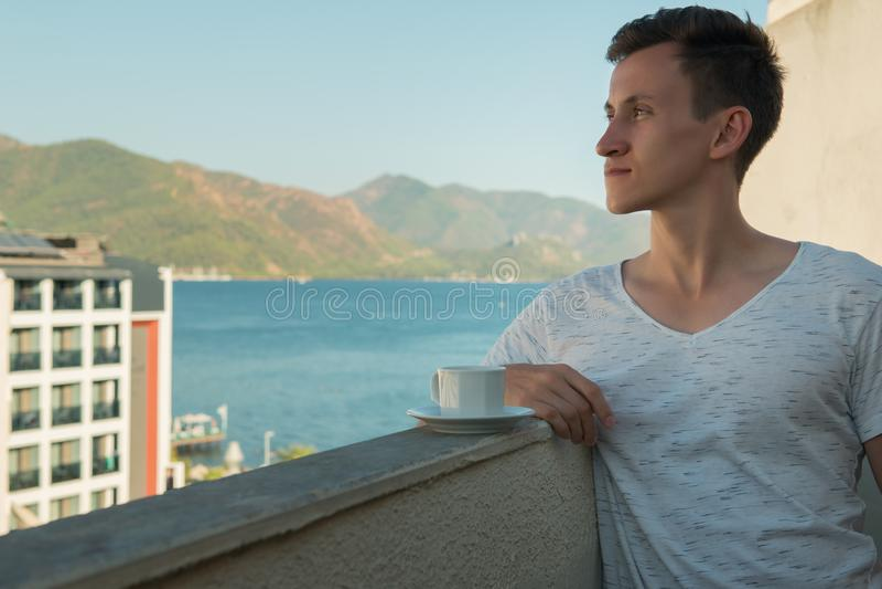 Hombre joven que bebe el café fragante mientras que se coloca en el balcón de su sitio en el hotel foto de archivo