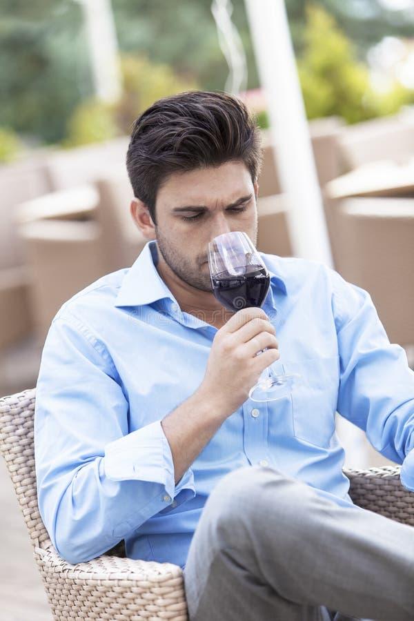 Hombre joven que bebe el vino rojo en el restaurante al aire libre fotografía de archivo libre de regalías
