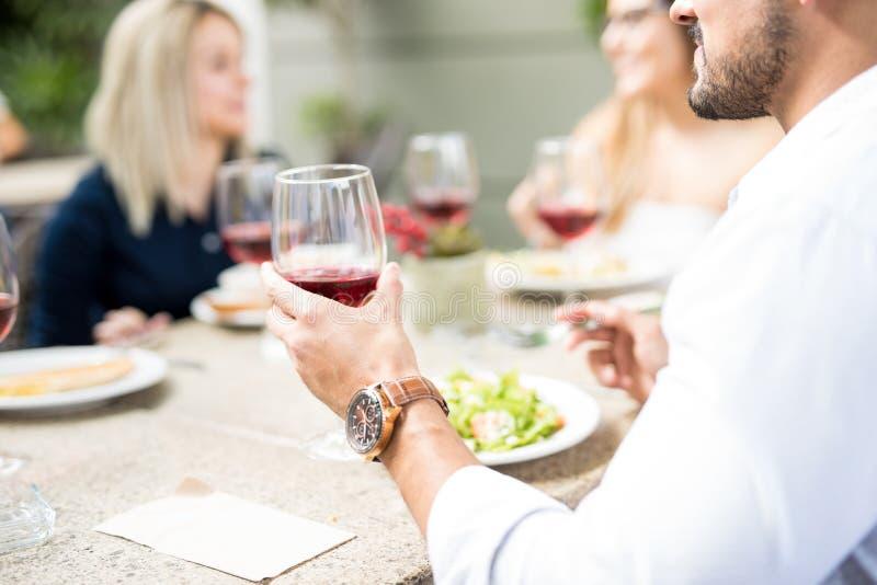 Hombre joven que bebe un poco de vino con los amigos imagenes de archivo